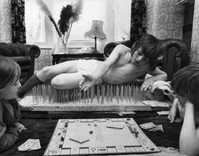 8-летний мальчик по имени Марк лежит на кровати из гвоздей, играя в «Монополию», Лондон, 1976 год.