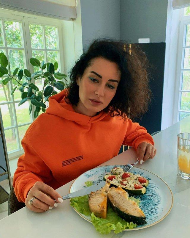 Тина Канделаки в оранжевом худи ест