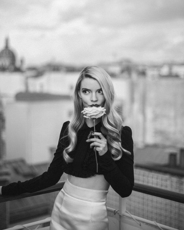 """Аня Тейлор-Джой - звезда сериала """"Ход Королевы"""" на балконе в черной кофте и цветком"""