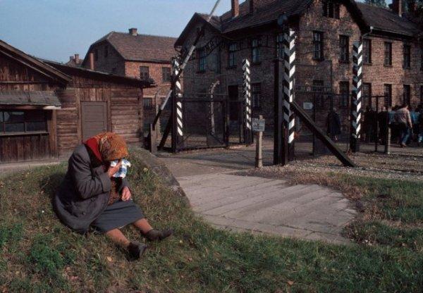 Женщина плачет у ворот музея концлагеря Аушвиц