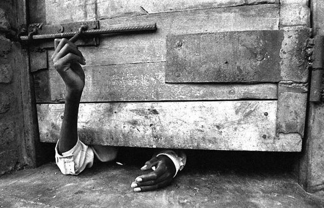 Человек пытается открыть дверь своей камеры в Кигали