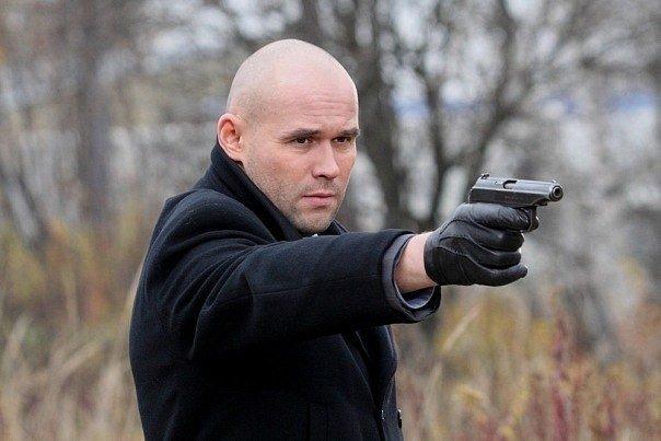 Максим Аверин в черном пальто с пистолетом