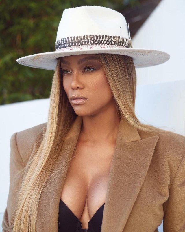 Тайра Бэнкс в коричневом пиджаке и белой шапке