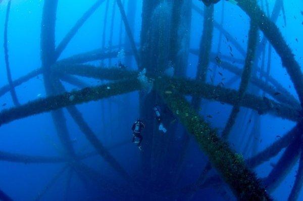 Дайвер на фоне подводной части нефтяной вышки