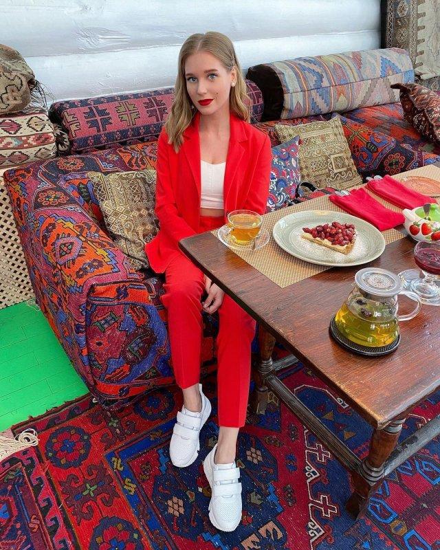 Кристина Асмус в красном костюме и белой кофте за столом