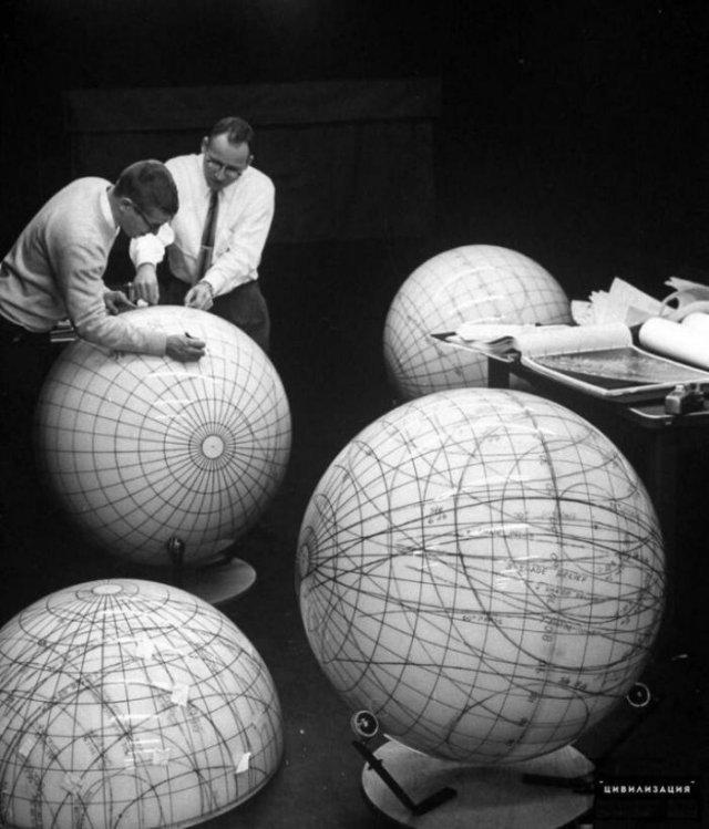 Ученые изучают фазы Луны на лунных глобусах в рамках подготовки к пилотируемому полету на Луну, 1960–е годы, США