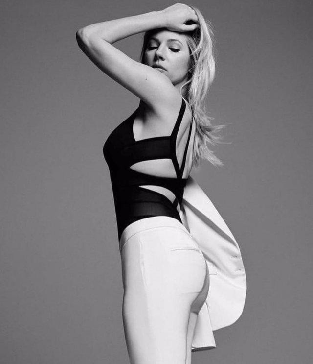 Кэтрин Уинник в черной кофте и белых штанах