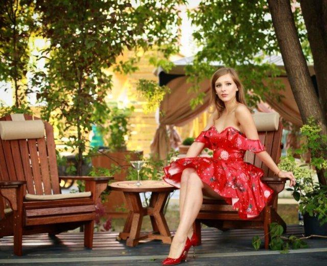 Лиза Арзамасова в красном платье на кресле