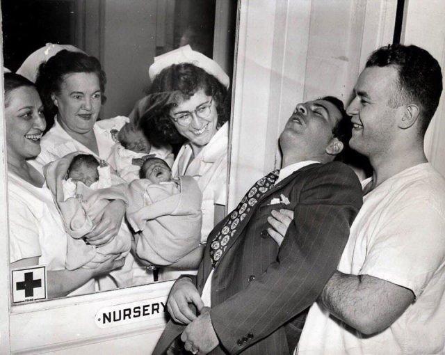 Сотрудники роддома показывают счастливому отцу его новорожденных тройняшек. Нью-Йорк, 1946 год