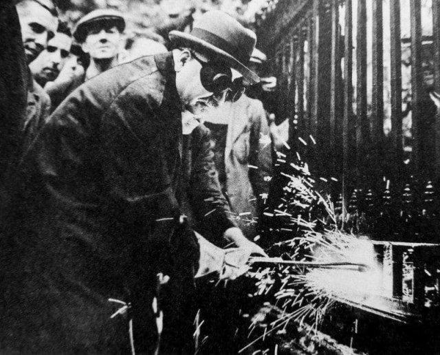 Посол в Великобритании Иван Михайлович Майский режет прутья решетчатого забора посольства СССР, чтобы пожертвовать металл на нужды военной промышленности. Лондон, Великобритания, 1943 год