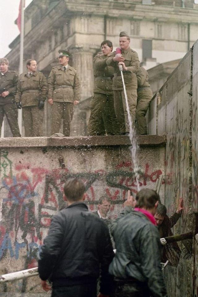 Пограничники ГДР обливают водой гражданских из ФРГ, которые рушат пограничную стену, 1989 год.