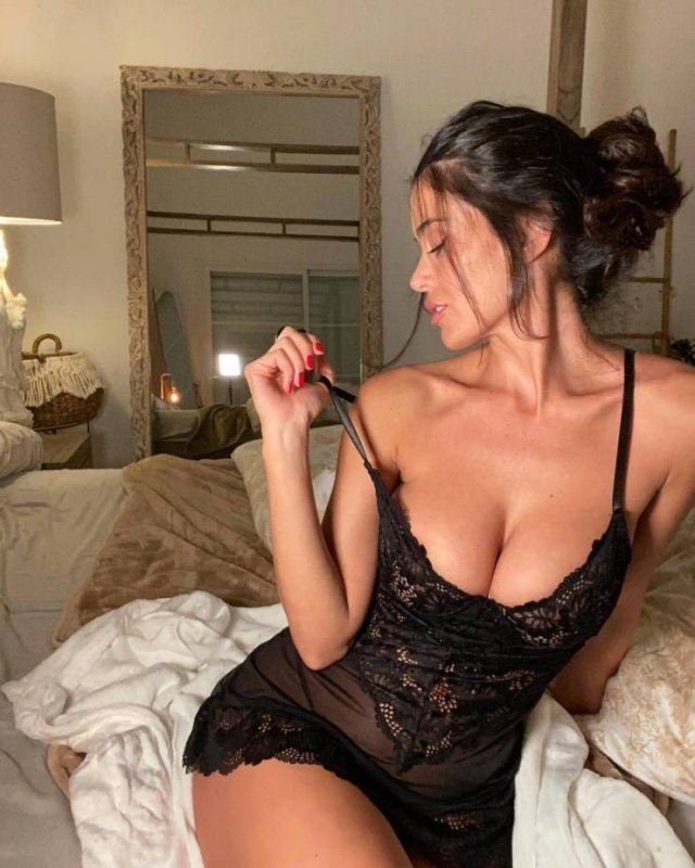 Девушка в черном боди на кровати