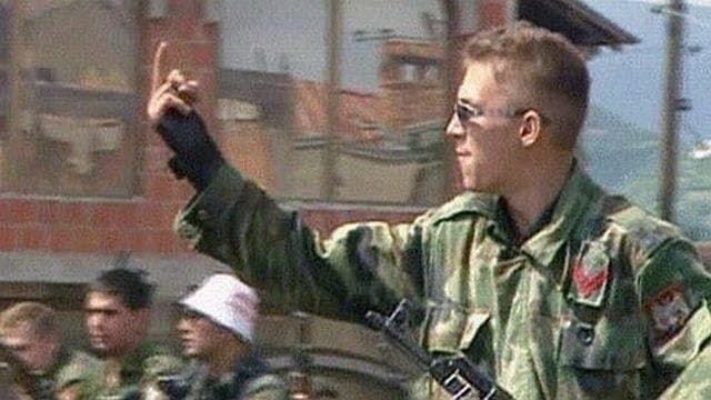 Югославский солдат показывает средний палец американским миротворцам