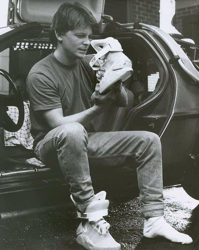"""Майкл Дж. Фокс рассматривает кроссовки """"из будущего"""" Nike MAG на съемках фильма """"Назад в будущее 2"""", 1989 год."""