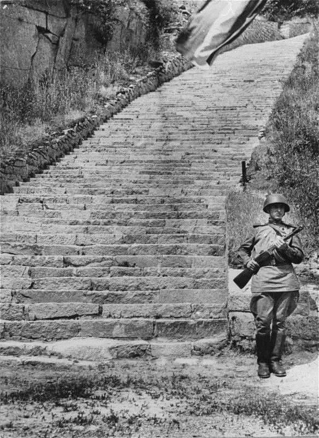 Cepжант Кpacной Aрмии на посту почетного караула у «лестницы смерти» в кapьере вблизи бывшeго концлагepя Маутхaузен. Лето 1945 г.