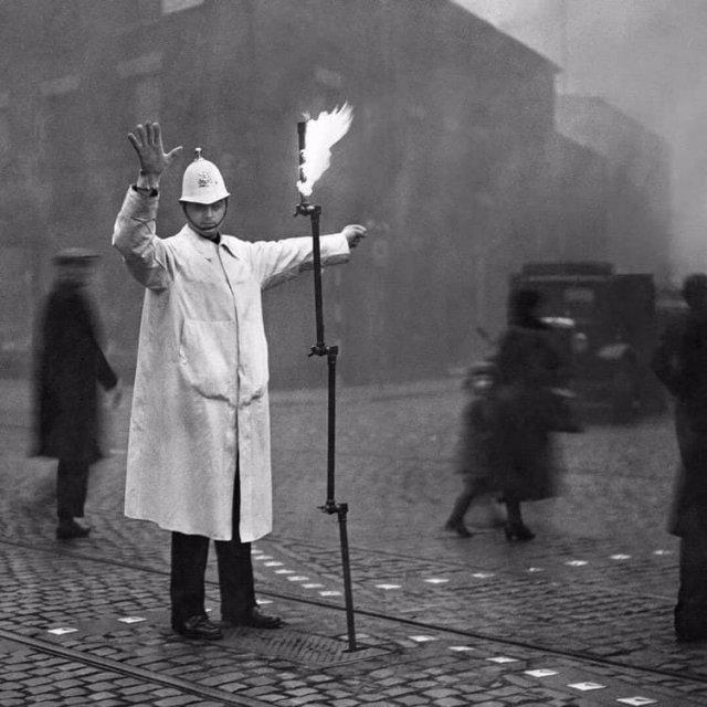 Регулировщик движения во время тумана использует в своей работе складное осветительное устройство, горящее от магистрального газа. Лондон, ноябрь 1935 года.
