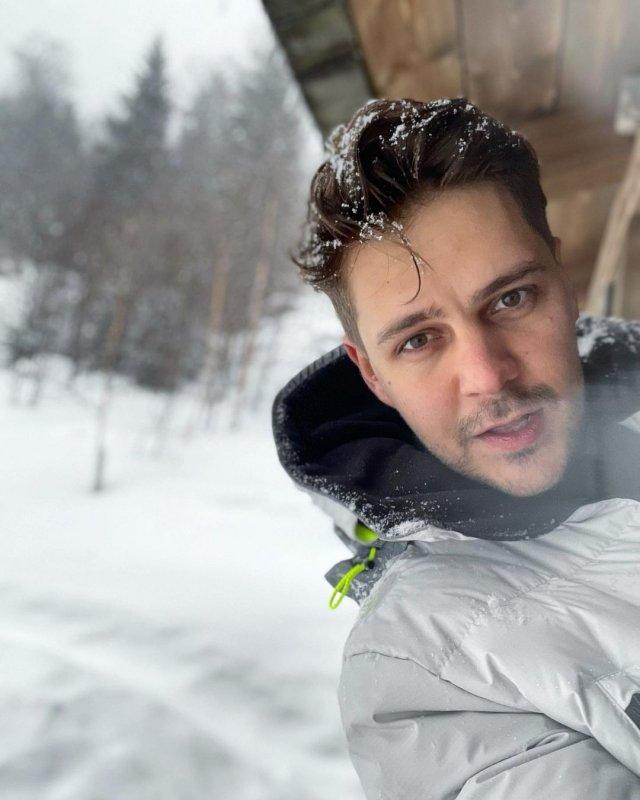 Милош Бикович в горах в белой куртке