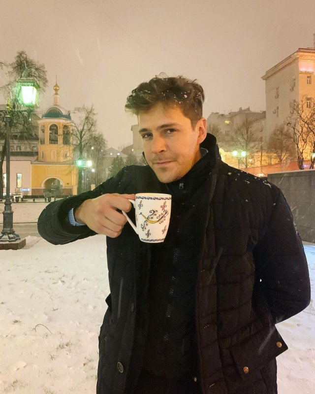 Милош Бикович на фоне церкви с чашкой