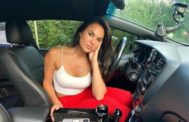 Автоблогер Анна (anna.motors) в салоне в белой кофте и красных штанах