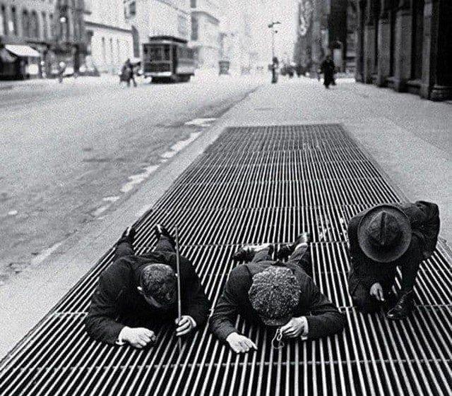 Мальчишки вылавливают мелкие монетки из вентиляционной решетки в Нью-Йорке во время Великой Депрессии, 1930 г.