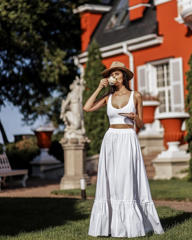 Алана Мамаева в белом платье на фоне дома