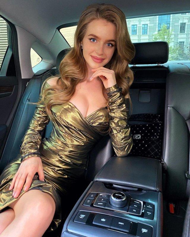Алина Санько в золотом платье с вырезом на заднем сидении машины