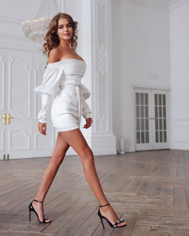 Алина Санько в белом платье и туфлях на каблуках