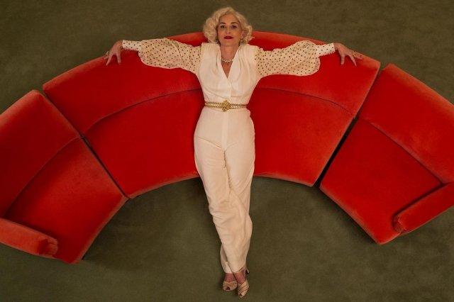 """Звезда фильма """"Основной инстинкт"""" Шэрон Стоун в белом костюме на красном диване"""