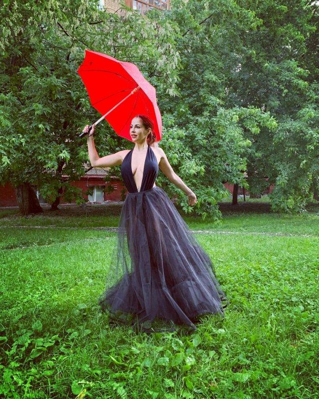 """Экс-звезда """"ДОМ-2"""" Елена Беркова в черном платье с красным зонтом"""