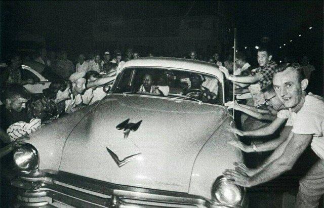 Толпа пытается перевернуть автомобиль с темнокожей семьей во время расовых беспорядков в г. Клинте, США. 1956