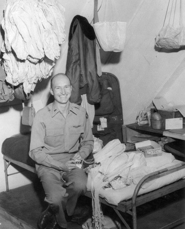 Американский пилот Гейл Хелворсен прикрепляет сладости к маленьким парашютам, которые сбросит для детей Восточного Берлина, находившегося в экономической блокаде. Германия. 1949 г.