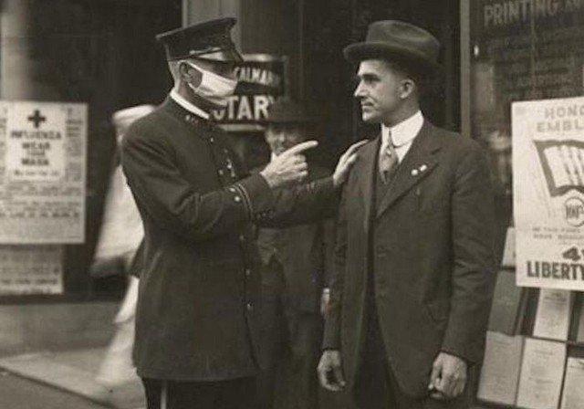Полицейский в Сан-Франциско делает предупреждение мужчине за то, что он не носит маску во время пандемии гриппа, 1918 год.