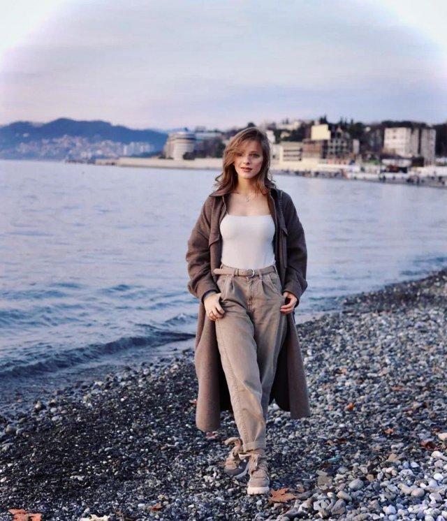 Лиза Арзамасова в белом костюме и накидке на берегу моря