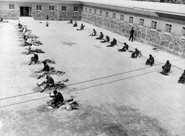 Заключенные дробят булыжники и шьют тюремную одежду. Роббенэйланд. ЮАР. 1964 год.