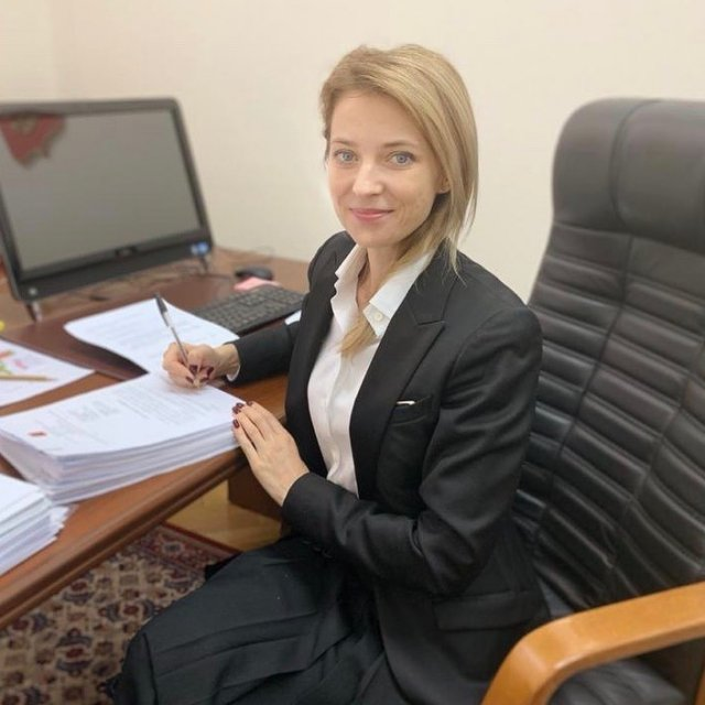 Политик Наталья Поклонская в черном пиджаке и белой рубашке за работой