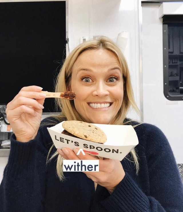 Риз Уизерспун ест печенье в черной кофте