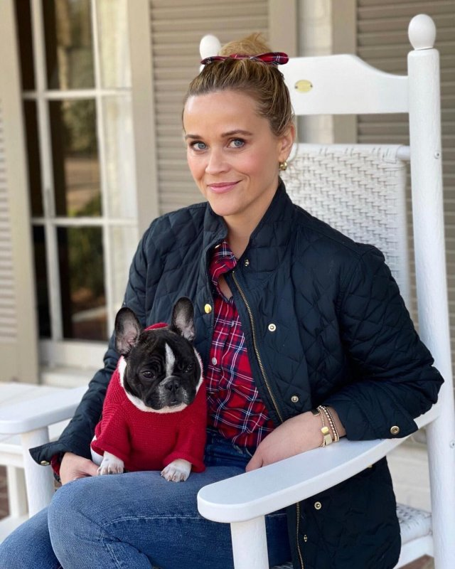 Риз Уизерспун в черной куртке с собакой на коленях