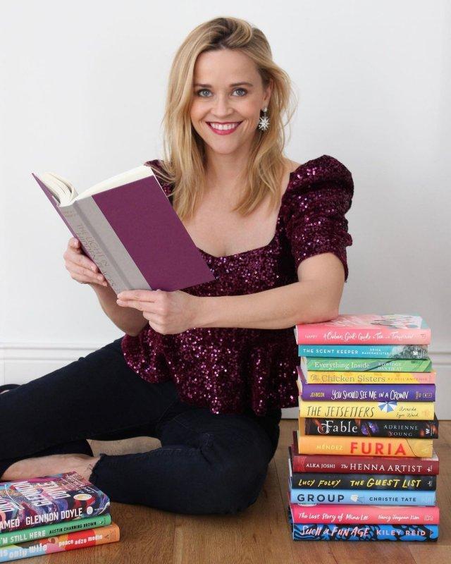 Риз Уизерспун в бардовой кофте с книгами