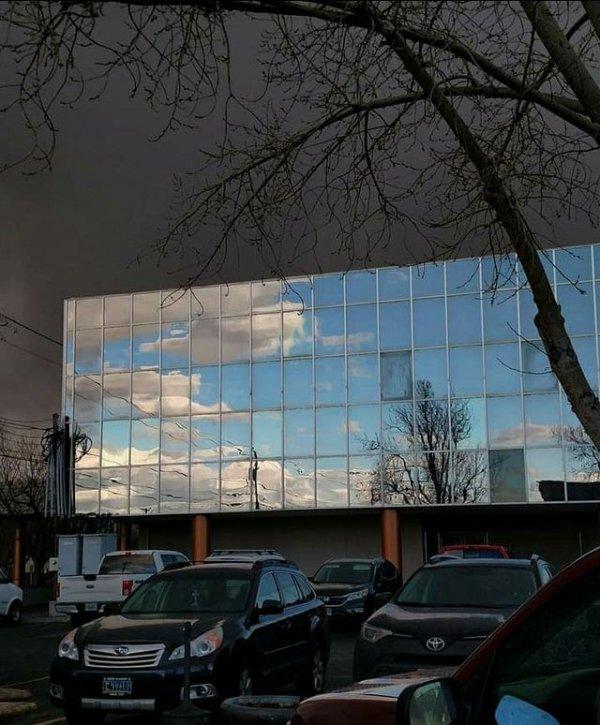 Голубое небо отражается в здании, а за ним гроза