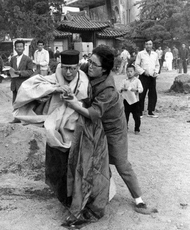 Женщина вырывает спички у буддийской монахини, облившей себя бензином. Южная Корея, 1963 год.