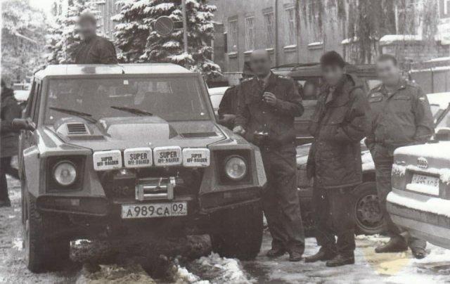 Милиционеры смотрят и фотографируют редкое авто Lamborghini LM002.