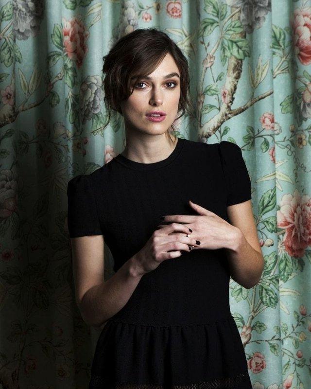 Кира Найтли в черном платье на фоне шторы