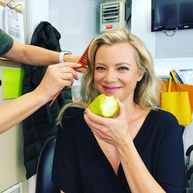 """Звезда фильма """"Эффект Бабочки"""" Эми Смарт ест яблоко в черной кофте"""