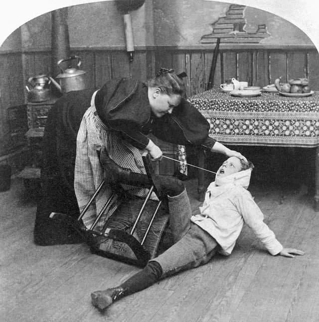 Мать вырывает у сына больной зуб. 1897 год