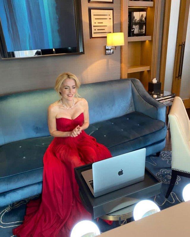 """Джиллиан Андерсон, звезда сериала """"Секретные материалы"""" в красном платье перед ноутубком на диване"""