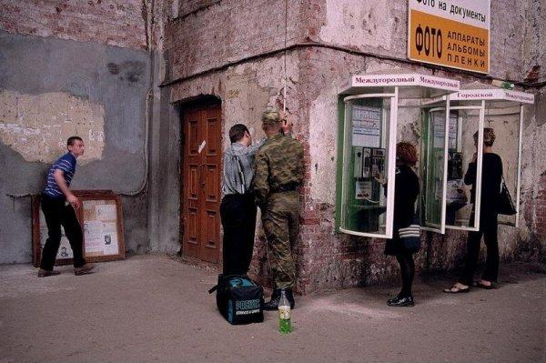 Люди звонят с уличного телефона на Балтийском вокзале. Россия, Санкт-Петербург, 1997 год.