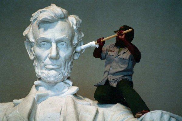 Рабочий чистит ухо статуе Авраама Линкольна