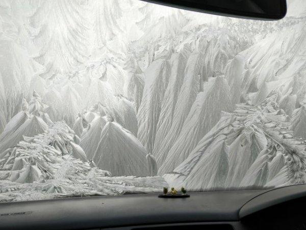 Это не лодка, плывущая мимо заснеженного горного пейзажа, а замёрзшее лобовое стекло
