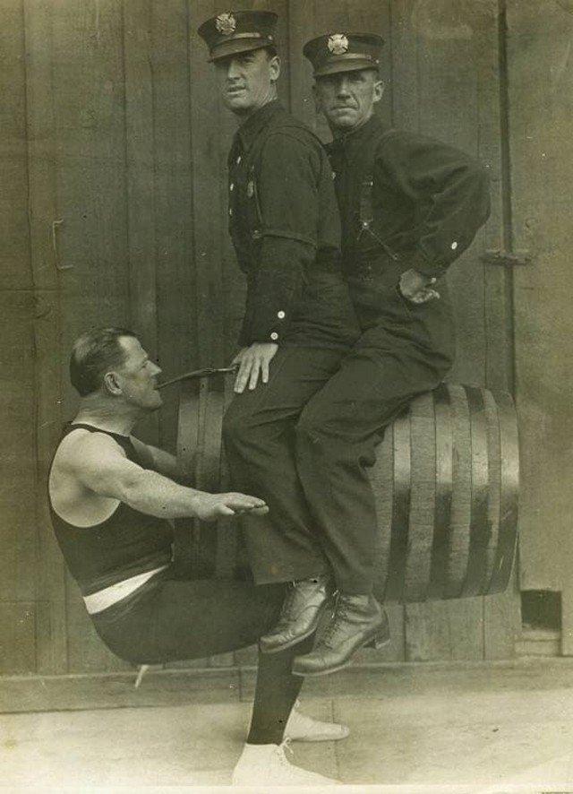 Гарри Ф. Гриффин, силач из пожарной охраны Лос-Анджелеса, держит зубами двух коллег, 1914 год.
