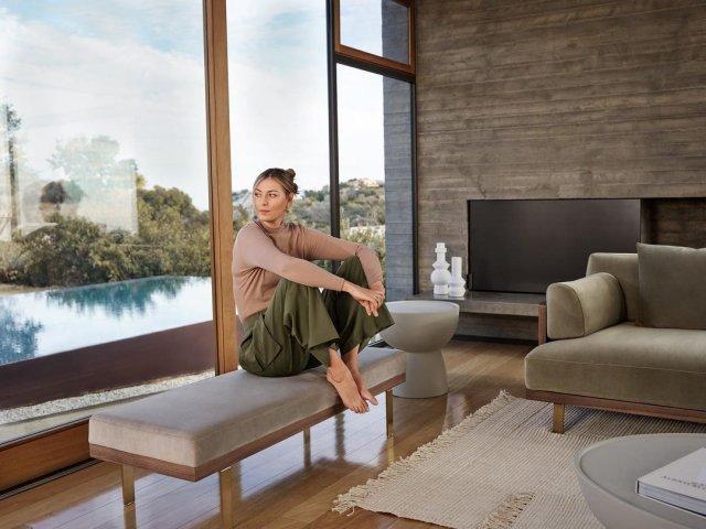 Мария Шарапова сидит в коричневой кофте и зеленых штанах у окна
